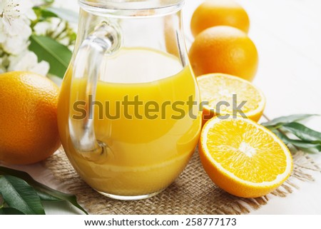 Orange juice  in the glass jug on the wooden table