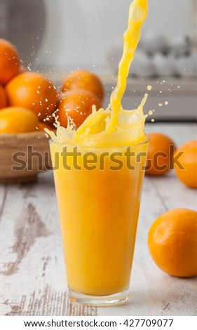 Orange juice poured in a glass with splash.