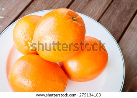 Orange on white plate put on wooden table.