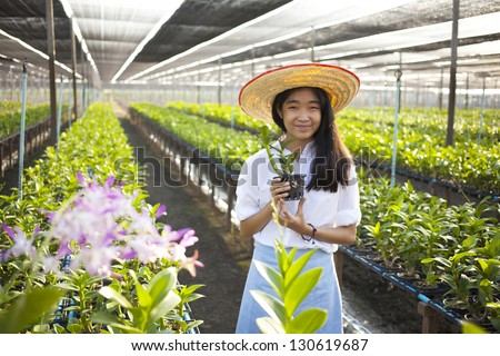 orchid and girl, Young Asian girl wearing weave hat in orchid farm