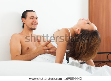 Ordinary couple having sex on bed in home interior