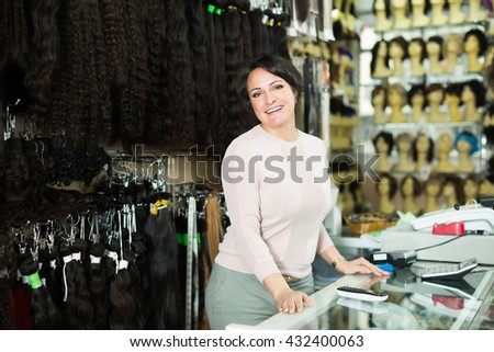 Ordinary female assistant selling natural hail ponytails, tresses and wigs