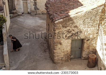 ORGOSOLO, ITALY-AUGUST 20, 2004: woman broom cleaning a narrow street in a traditional village of Sardinia, in Orgosolo.