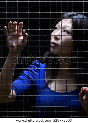 Oriental woman, trapped behind an iron fence