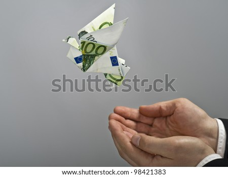 Origami bird made by euro bill, flying away