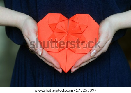 Origami heart in hands.