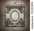 Ornamental silver frame on an aged damask wallpaper - stock photo