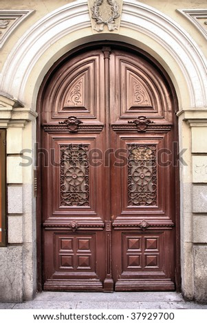 Ornamental wooden door in Madrid, Spain. Old architecture.