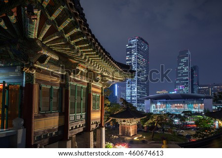Ornate building at the Bongeunsa Temple and view of Gangnam in Seoul, South Korea at night.