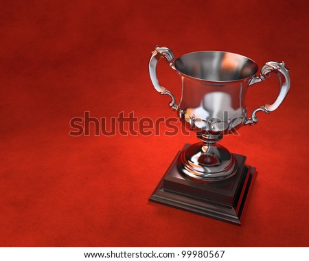 Ornate trophy cup on wooden plinth with red background. Includes copy space.