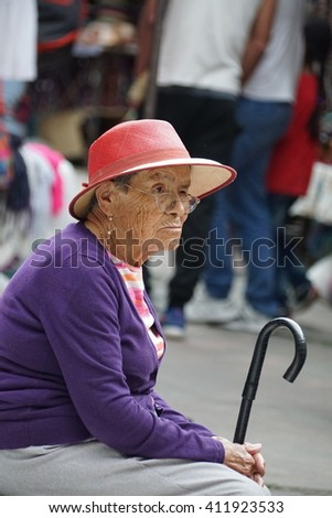 OTAVALO, ECUADOR - APRIL 15, 2016:Woman in a purple sweater and pink hat, with a cane, in the Otavalo Market