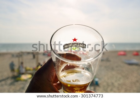 OUDDORP, NETHERLANDS- JULY 11, 2015: A Glass of beer Heineken  on the beach looking at sunset. Heineken Lager Beer is a pale lager beer produced by the Dutch brewing company Heineken International