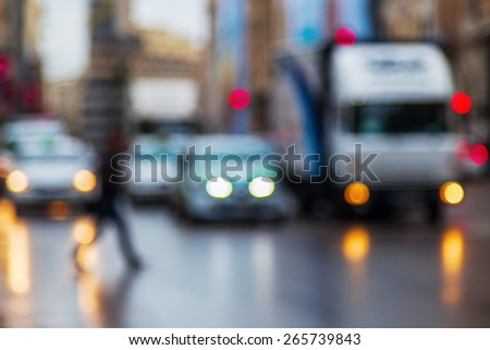 out of focus picture of city traffic with crossing people on a rainy day at dawn