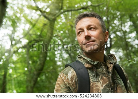 Outdoor autumn male portrait. Handsome middle-aged man posing in forest, image toned and noise added.