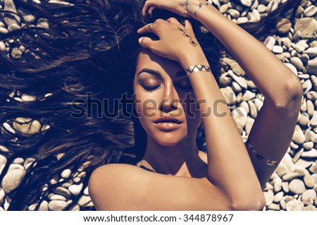 Outdoor fashion portrait of sexy lady lying at beach