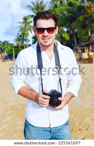 Outdoor fashion portrait of young handsome man photographer with camera posing on the tropic island beach smiling and having fun in summer