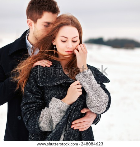 Outdoor fashion sensual portrait of young beautiful happy stylish couple in love standing in cold windy winter full of snow field