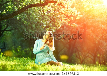 Outdoor portrait of a beautiful woman in dress among apple blossoms