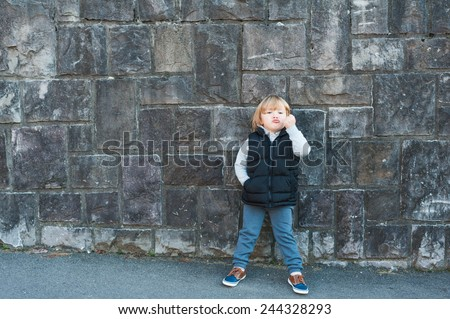 Outdoor portrait of a cute little boy against stone wall