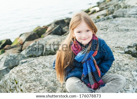 Outdoor portrait of a cute little girl next to lake on a nice day