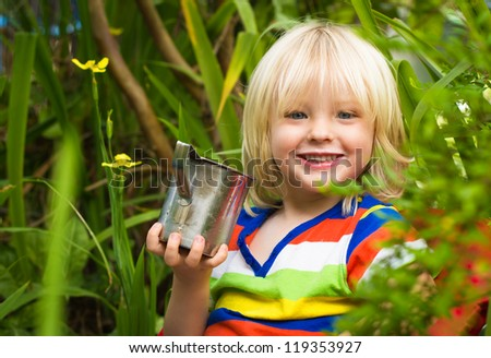 Outdoor portrait of a cute smiling child drinking milk in the garden looking at camera