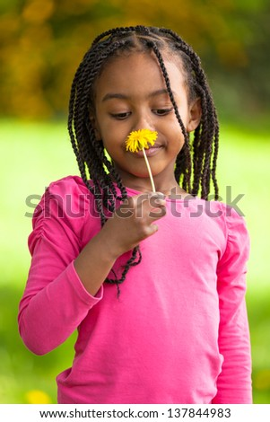Outdoor portrait of a cute young black girl holding a dandelion flower - African people