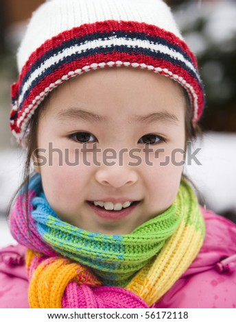 outdoor portrait of a 9-year old asian girl in colorful winter outfits