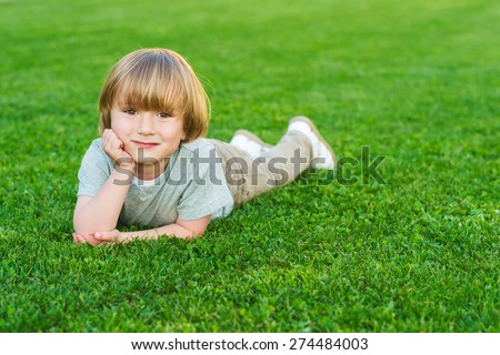 Outdoor portrait of adorable little blond boy laying on a bright fresh green lawn