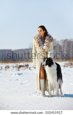 outdoor portrait of beautiful brunette woman with borzoi in snowy filed with winter forest on background