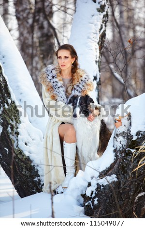 outdoor portrait of beautiful brunette woman with russian wolfhound in snowy winter forest