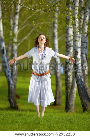 outdoor portrait of beautiful hippie girl jumping on green grass in birch forest