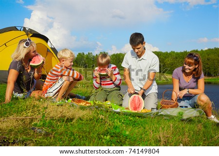 outdoor portrait of happy families at the picnic eating watermelon