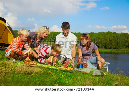 outdoor portrait of happy families at the picnic, going to eat watermelon cut in two halfs.