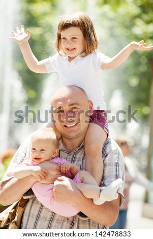 Outdoor portrait of happy father with two adorable daughters
