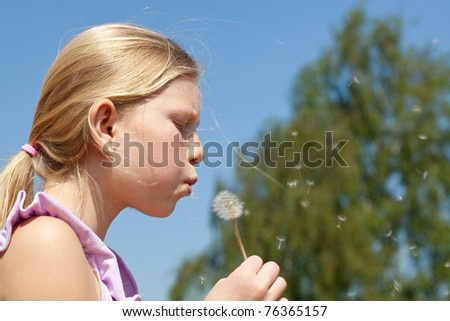 Outdoor portrait of teenager girl puffing to dandelion