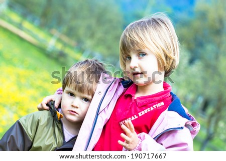 Outdoor portrait of two embracing cute little girls