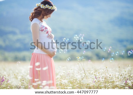 Outdoor portrait of unrecognizable young pregnant woman in the field. beautiful pregnant woman in wreath relaxing in the summer nature meadow. pregnant woman relaxing in flowers