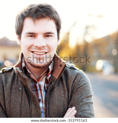 Outdoor spring portrait of young handsome man smiling and having fun outdoor