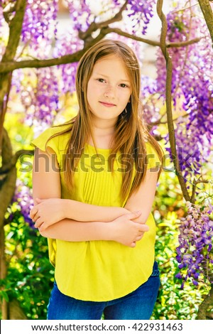 Outdoor stylish vertical portrait of a cute little girl of 8-9 years old, standing next to beautiful purple wisteria flowers, wearing green blouse, arms crossed