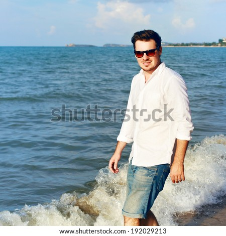 Outdoor summer portrait of smiling happy man in jeans shorts and white shirt on the beach near the sea blue sky and sun, walking and having fun on tropic island