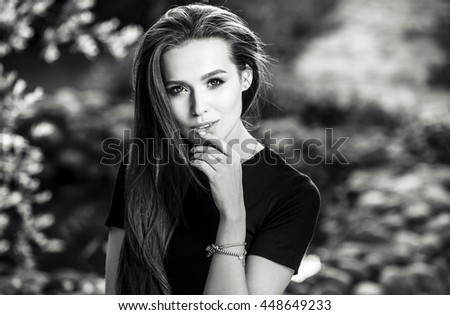 Outdoors black-white portrait of beautiful young long hair brunette woman.