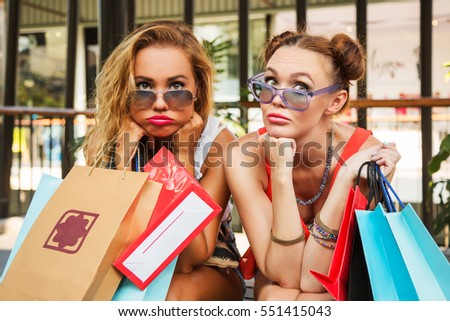 Outdoors fashion portrait of two young beautiful girl friends in shopping mall with a lot of shopping bags. Funny faces and and tired after successful shopping. Wearing stylish t-shirts and sunglasses