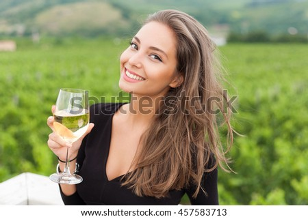 Outdoors portrait of a beautiful wine tasting tourist woman.