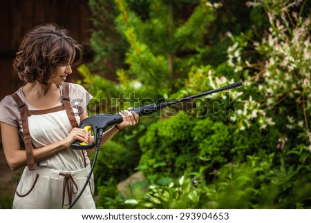 Outdoors portrait of beautiful & positive young woman in overalls which posing with water-cannon in summer garden.