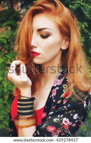 Outdoors portrait of beautiful woman with red hair and bright makeup. Accessories. Hairstyle. Boho, hippie vibe, stylish vintage bohemian outfits
