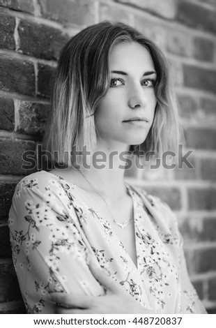Outdoors portrait of beautiful young woman. In black and white toned.