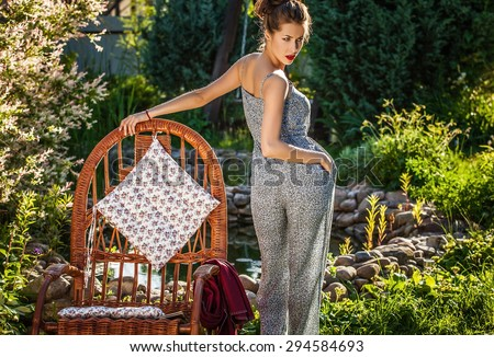 Outdoors portrait of beautiful young woman which stay near rattan rocking-chair in evening summer garden.