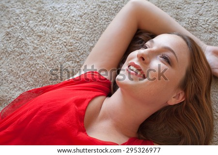Over head beauty portrait of an attractive young woman laying on a bed, in a bright red dress, looking happy and smiling joyfully, home interior. Beautiful woman lifestyle, relaxing indoors space.