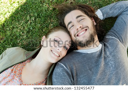 Over head close up portrait of a young bohemian couple laying down on green grass with their heads together in a sunny park, smiling.