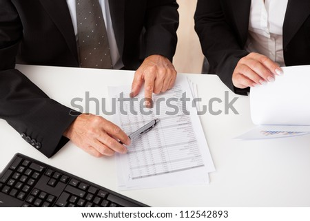 Overhead cropped view of hands with a document on a table top at a business meeting in progress